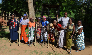women-each-holding-a-measuring-stick-for-their-cleome-plots-prepare-to-sing-after-sowing-seed